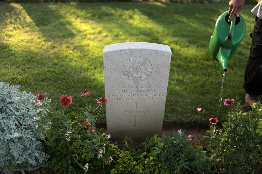 A guard waters flowers planted next to the grave of Corporal Thomas Browne in Deir El Belah War Cemetery, in the central Gaza Strip